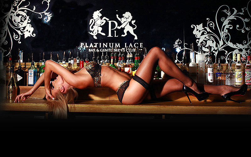 A woman in underwear and suspenders lying on her back on top of a bar