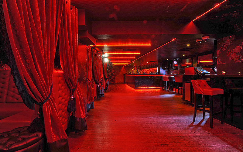 Red booths with curtains and high-chairs at Babble City, London