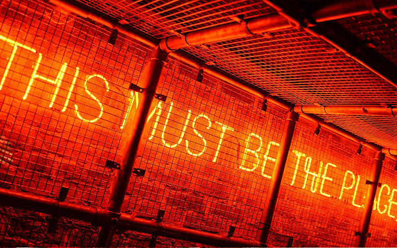 A lit up sign reading This Must Be The Place on a brick wall behind cages