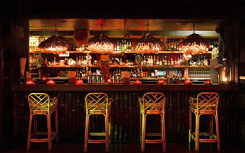 Bamboo bar with four wooden high-seats at Kanaloa Club, London