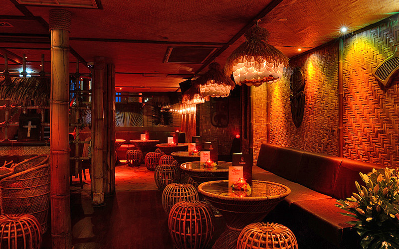 Round tables with bamboo seats, booths and sofas lining the walls at Kanaloa Club, London