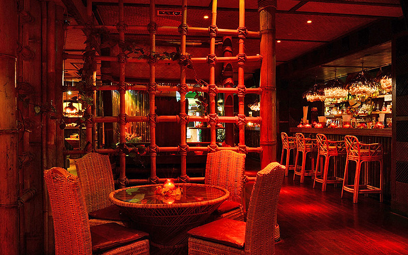A table with four chairs, and four bamboo chairs at the bar in the background, at Kanaloa Club, London