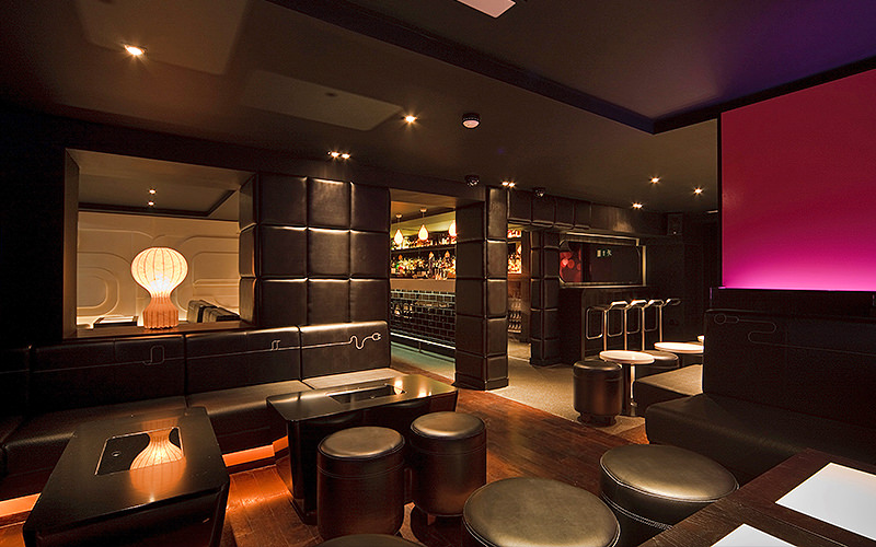 Sitting area in a nightclub, low tables, black leather stools, faux leather walls