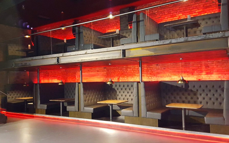 Two floors of booth seating with atmospheric, red lighting in the background