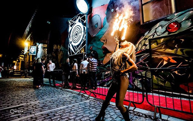 A woman fire breathing outside Fusion nightclub, with the queue to get in, in the background
