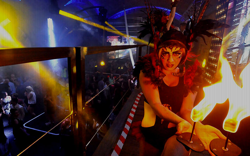 A woman performing in Level nightclub with fire on sticks