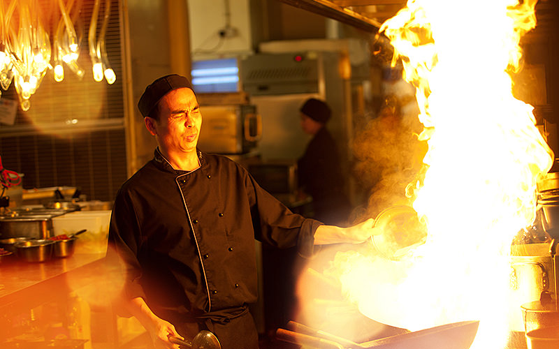 A chef in black pulling a face at fire coming out of the pan