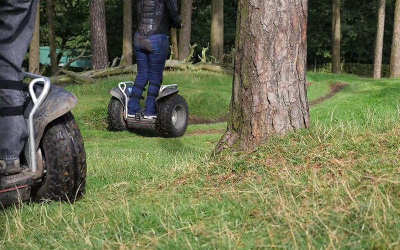 Two people riding segways around a forest track