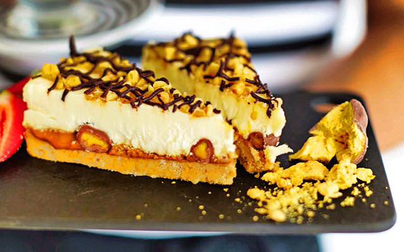 Two pieces of cheesecake on a slate