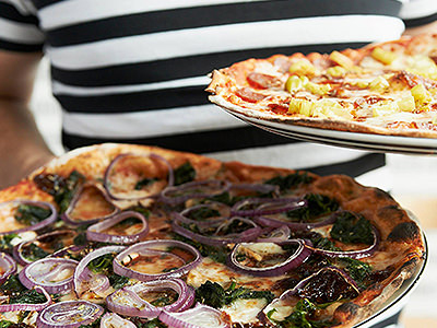 Close up of a man in a black and white striped top serving up two different pizzas