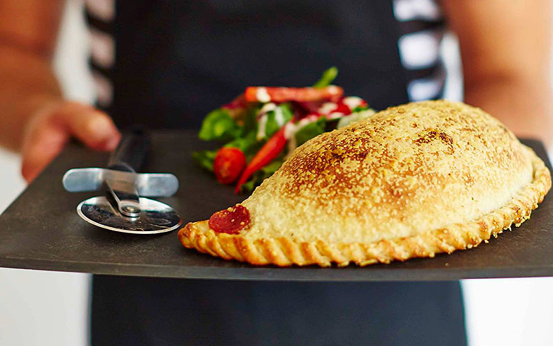 Calzone, salad and a pizza cutter on a slate being served up