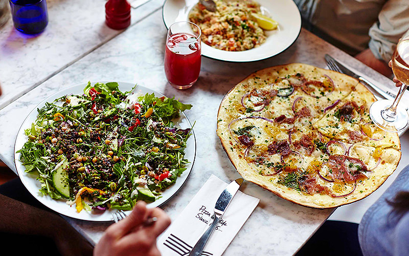 Three plates of pizza, salad and risotto laid out on a table alongside a red drink
