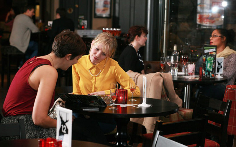 Two women reading a menu at the table, with people sat at tables in the background