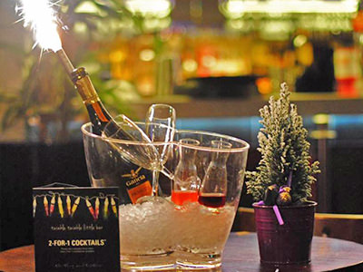 A bottle of champagne and glasses in a transparent ice bucket, with a lit up sparkler in the bottle