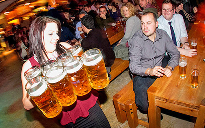 A woman holding eight full steins in her hands, with people watching in the background