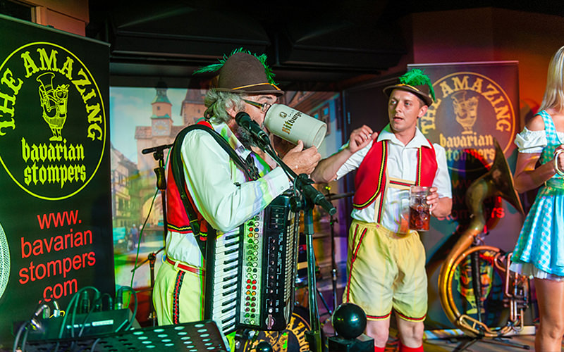 Men on stage in traditional Bavarian on stage, with one man playing the accordian and drinking from a stein