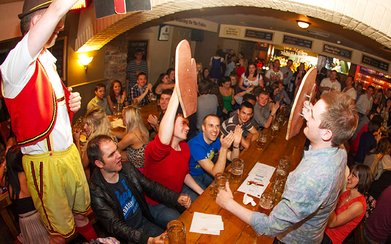 Two men hlding giant hand paddles at a table full of people with a man in traditional Bavarian clothing shouting them on