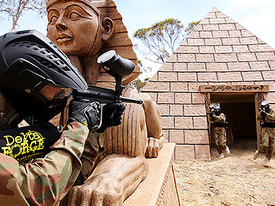 A person with a paintball gun hiding around a statue of a Pharaoh, as two other people stand at the door of the pyramid with paintball guns