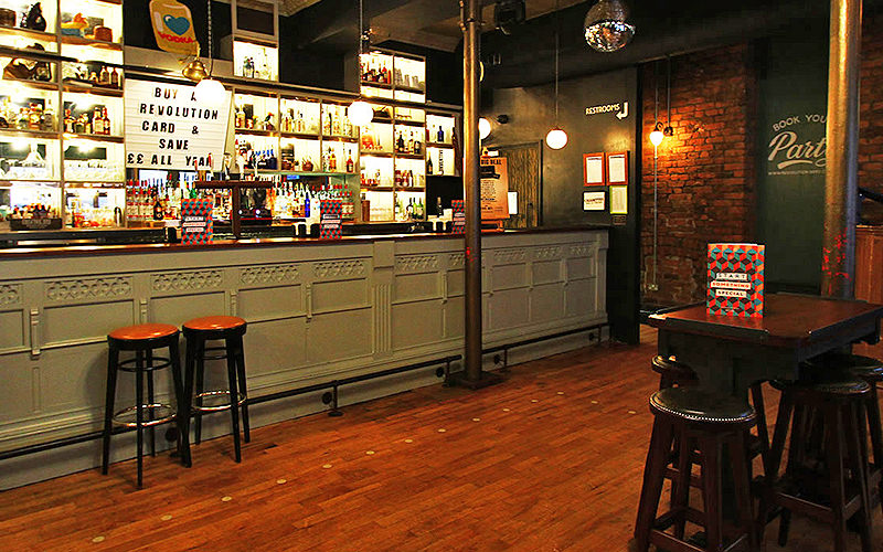 The bar area, with stools and tables in the foreground, at Revolution Wood Street, Liverpool