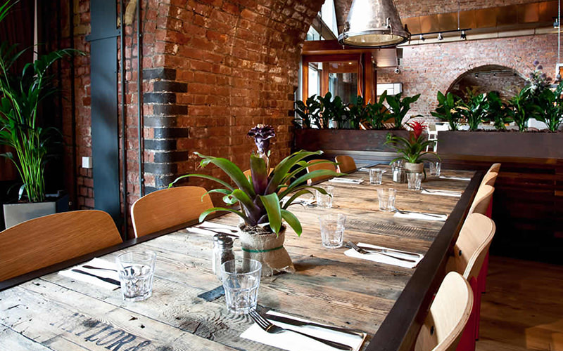 A long table set for dinner in an exposed brick room