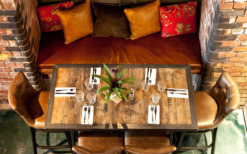 Birds eye view of a table set for dinner with leather chairs and a leather sofa along the wall