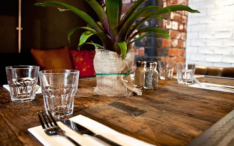 Cutlery, glasses and a plant on a table set up for dinner