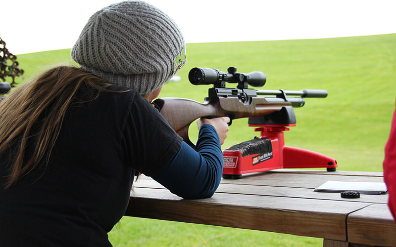Woman in a grey beanie hat aiming her gun forwards as she prepares to fire