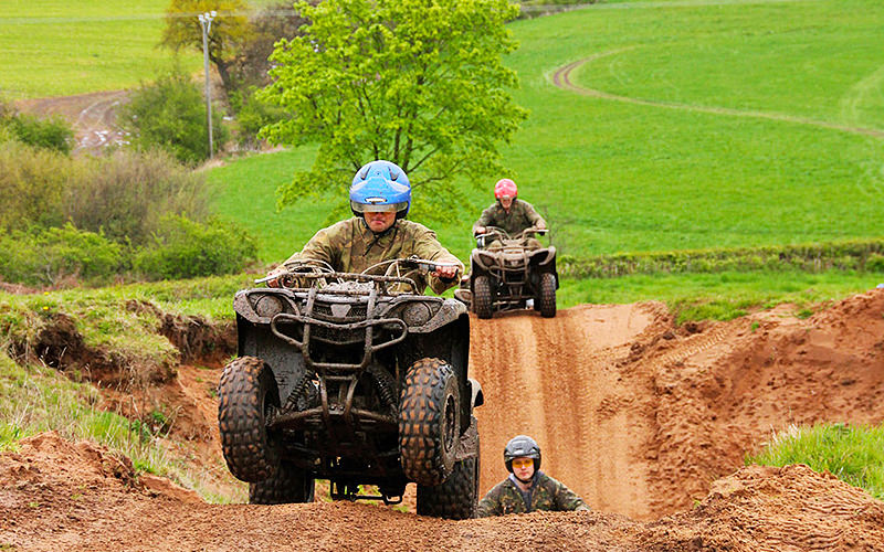 Three men driving quad bikes over rough, muddy terrain