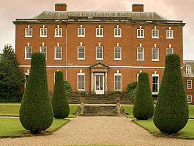 The exterior of Catton Hall, with topiary trees lining the entrance path