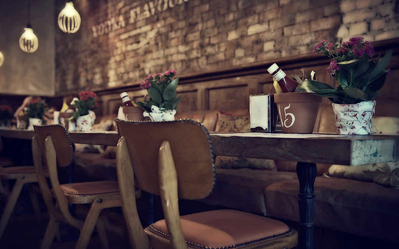 Wooden chairs tucked under tables lining the exposed brick wall