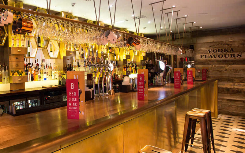 Menus on a bar counter, with stools lined up along the front