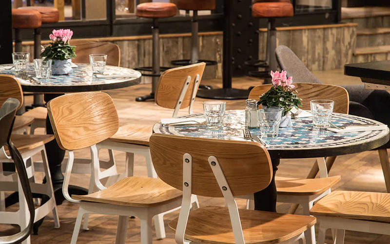 Wooden chairs and circular tables set up for dinner