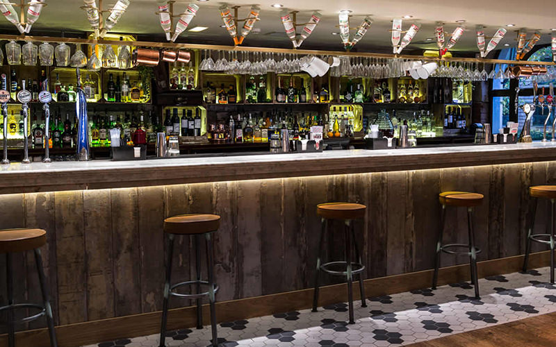 Wooden bar with stools lined along the front