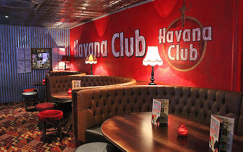 The red Havana Club wall with brown leather booths in front