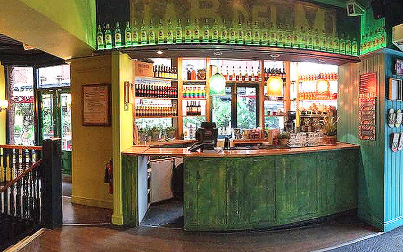 The green bar, with bottles lined along the top, at Bar Salsa, London