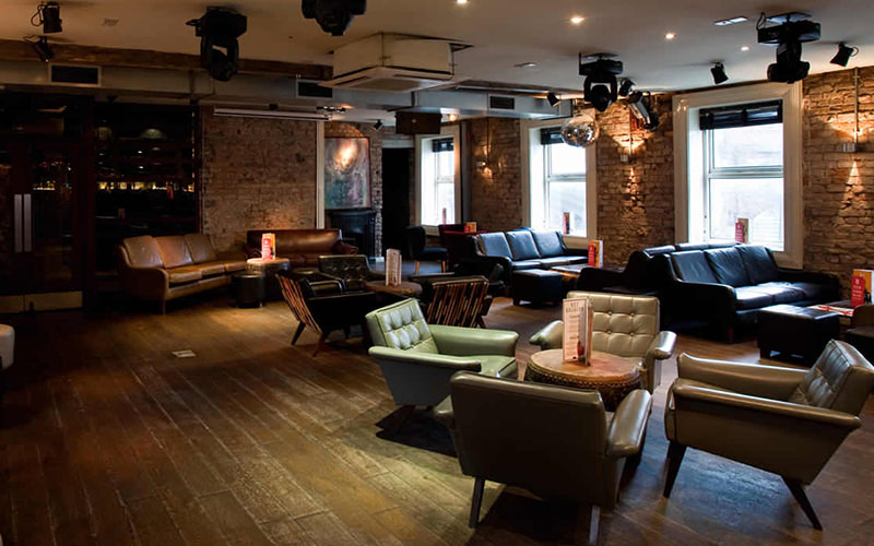 Leather chairs around circular tables in an exposed brick room