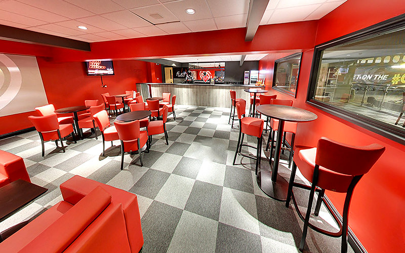 Red chairs and tables in the viewing room of Team Sport West London