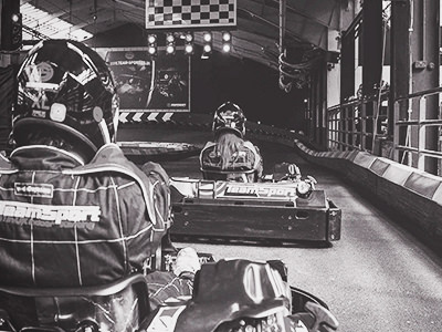 A black and white image of two people go-karting