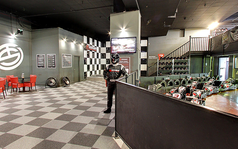 A man in racing gear and helmet stood next to an indoor go karting track