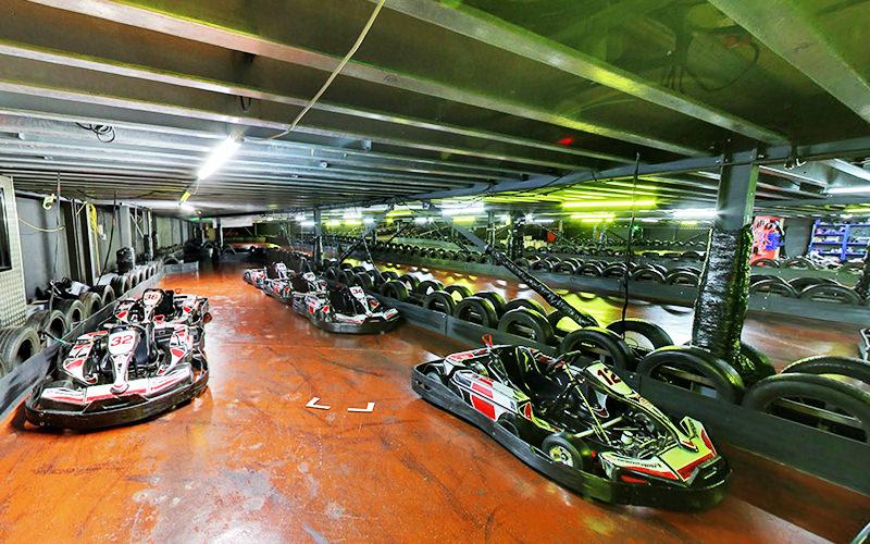 Go Karts lined up on an indoor karting track