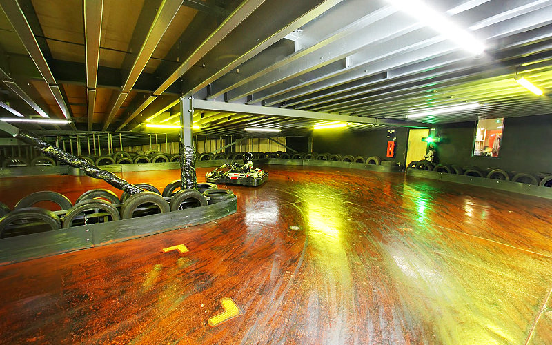 An empty, indoor go karting track surrounded by tyres