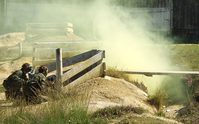 Two people playing paintball in a field, and hiding behind a fence with smoke in front