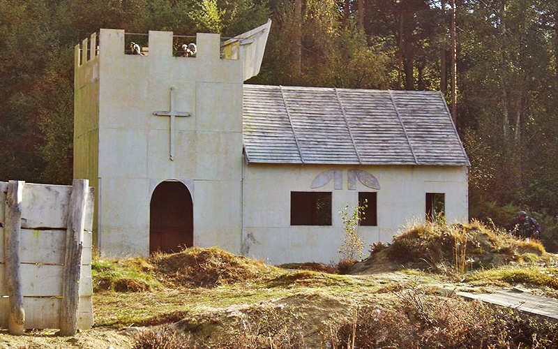 An abandoned white church on a field