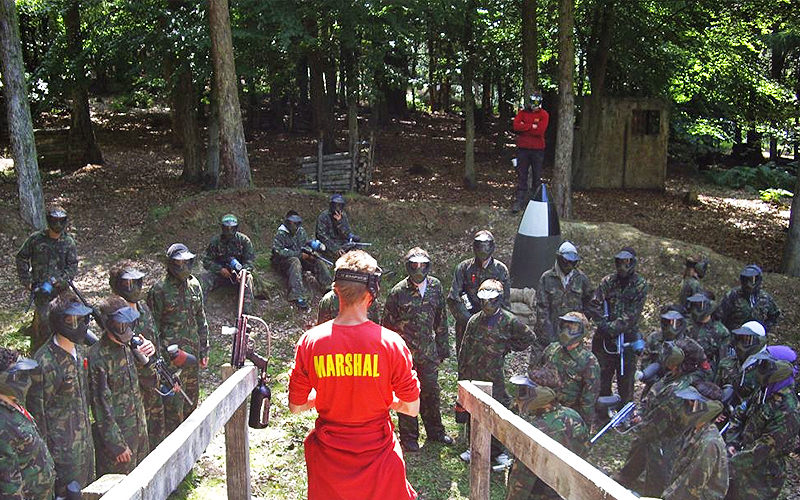 An instructor in red speaking to people playing paintball