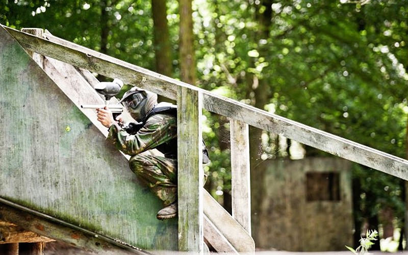 A person playing paintball on a roof