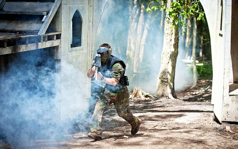 Man in camouflage and holding a paintball gun in a field