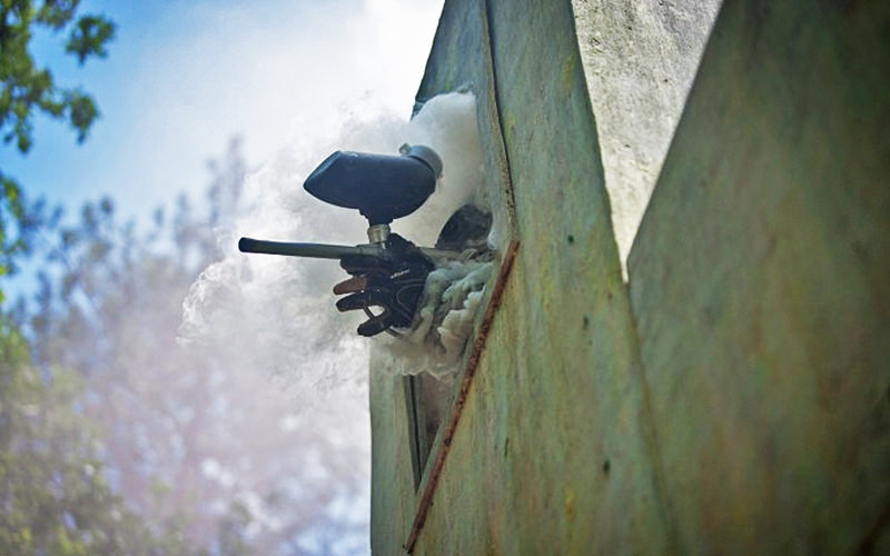 Hand holding a paintball gun out of a window