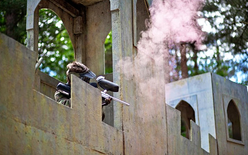 Person hiding behind a wall playing paintball