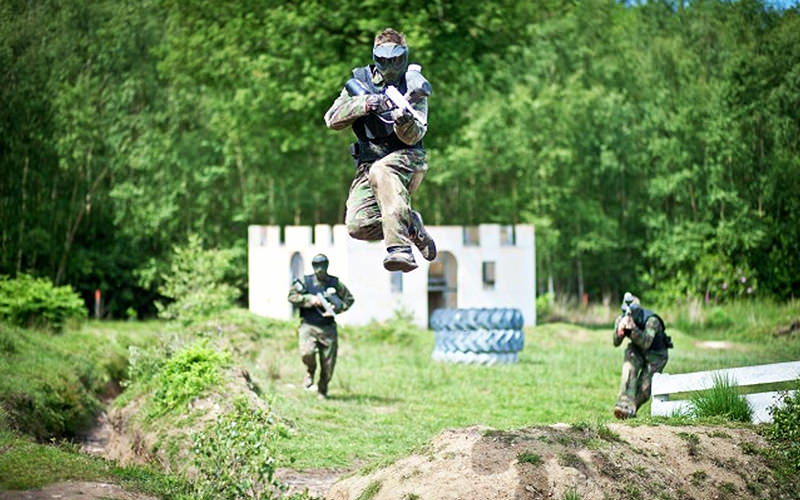 A man jumping in the ar whilst playing paintball
