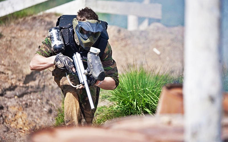 A man in camouflage, crouching down and holding a paintball gun